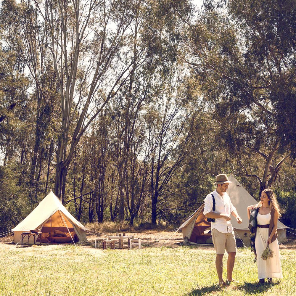 Campers standing in front of Psyclone High Quality Bell Tents in bushland